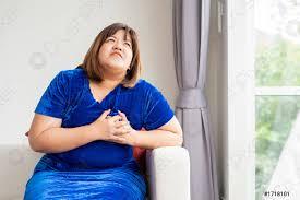 foto auf lager übergewichtige asiatische frauen sitzen auf dem sofa im wohnzimmer und greifen sich aufgrund herzerkrankungen krankheit und