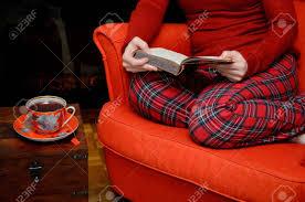 sitzt in einem sessel in gemütlichen schöner wohnen ein buch zu lesen und durch den kamin trinken