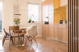 moderne skandinavische freifläche interieur der küche und esszimmer mit designmöbeln schwarze kühlschrank marmorwänden und braunem holzparkett aus