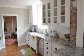 100 backsplash with white cabinets and grey countertop