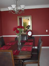 Dining Room Red Wall Theme And Dark Brown Wooden Set Under White Chandeliers Lamp