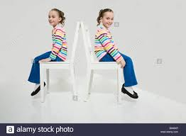 Twin Sisters Sitting On Chairs Stock Photo: 17303434 - Alamy