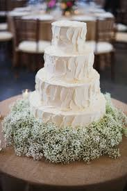 Simple White Four Layer Wedding Cake With Babys Breath Flowers At Base