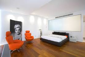 Simple Studio Apartment Unique Bold Orange Chairs White Walls Bedding Black Bed Finished Wooden