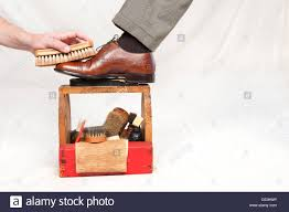 A Man Gets His Shoes Polished By Worker Using Vintage Shoe Shine Box