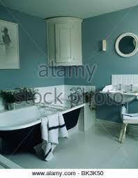 roll top badewanne und weiße wand eckschrank in grau blau