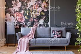 pulver rosa decke geworfen auf graue in echtes foto dunklen wohnzimmer interieur mit blumentapete gold le und vertäfelung an wand