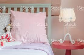 mädchen im schlafzimmer in rosa farbe ton mit puppe auf bett stockfoto und mehr bilder behaglich
