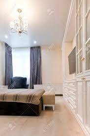 schlafzimmer in hellen farben mit dunklen bett und blauen vorhängen