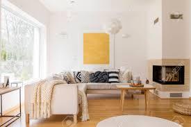 kerzen auf holztisch nahe bei kamin im geräumigen wohnzimmer mit weidenpuff auf boden