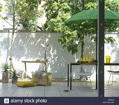 Green Umbrella Above Table And Wire Mesh Chairs On White Ceramic ...