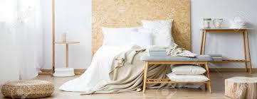hocker und holz in warmem natürlichem schlafzimmer mit weißen kissen auf bett oder bank nahe tisch mit kerzen