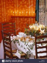 Arrangement Of Christmas Flowers And Lighted Candles On Table With White Cloth Antique Ladder Back Chairs In Dining Room