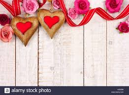 Two Valentines Day Wood Hearts With Roses And Ribbon Top Border Against A Rustic White Background Copy Space