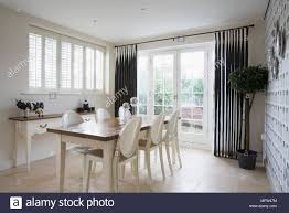 Wooden Dining Table And White Plastic Chairs In Room With Black Curtains