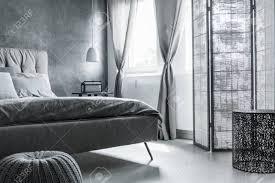 einfaches komfortables schlafzimmer mit grauer wand weicher bettwäsche und trennwand
