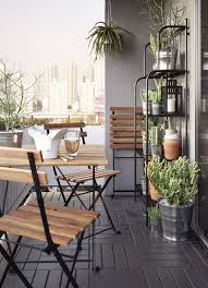 A Small Balcony Furnished With Foldable Table And Three Chairs All In Solid