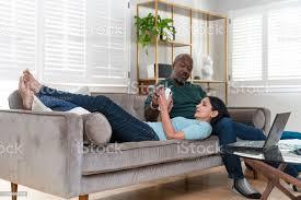 das reife glückliche familienpaar ruht im wohnzimmer der mann saß auf einer die frau liege mit dem kopf auf seinen runden und benutze ein