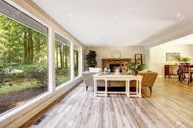 geräumiges helles wohnzimmer mit gemauerten kamin weißen tisch und glaswand