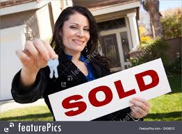 Happy Attractive Hispanic Woman Holding Keys And Sold Sign In Front Of House