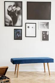 navy blue bench against white wall with gallery of posters in living