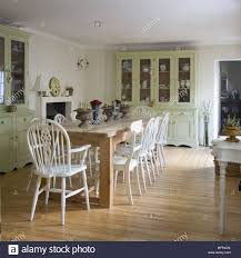 Wooden Table And White Painted Chairs In Centre Of Country Style Dining Room
