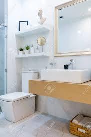 geräumiges und helles modernes badezimmer mit weißen wänden einer duschkabine mit glaswand einer toilette und einem waschbecken