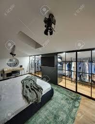 wunderschöne moderne schlafzimmer mit garderobe mit leuchtenden len weiße wände auf dem boden ist grün teppich dort auch gibt es bett tisch mit