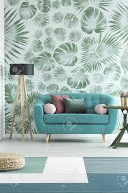 blaues sofa und hölzerne le gegen weiße tapete mit grünen monstera blättern im natürlichen wohnzimmer innenraum