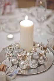 Simple White Candle On A Small Silver Platter Surrounded By Ornaments For Winter Wedding Centerpiece
