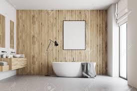 badezimmer aus holz mit betonboden großem fenster doppelwaschbecken und weißer badewanne ein gerahmtes vertikales poster an der wand mock der