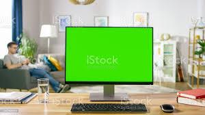 moderner pc mit grünen mockupdisplay auf dem schreibtisch in das gemütliche wohnzimmer stehen ein mann mit handy entspannt in seinem stuhl stockfoto
