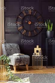 große uhr auf die schwarze wand sessel tisch und pflanze in einem wohnzimmer interieur echtes foto stockfoto und mehr bilder blumentopf