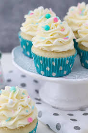 A Small White Cake Stand With Vanilla Cupcakes That Have Teal Polka Dot Liners The