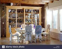 Painted Chairs With Tie-back Loose Covers At Rustic Table In ...