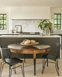 A Vintage Round Dining Table With Black Legs And Modern Industrial Chairs To Create