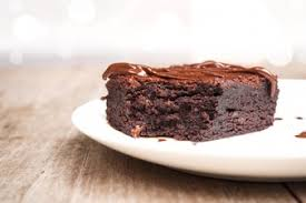Homemade brownies on white plate With chocolate fudge topping Over wooden background