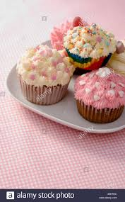 An English Cream Tea Cupcakes Decorated With Icing And Sprinkles