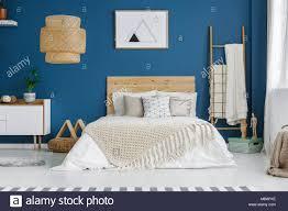 gestrickte decke auf holz bett im blauen schlafzimmer