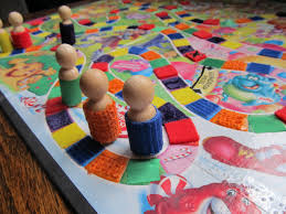 Wooden Game Pieces Shaped Like Little People With Different Textured Clothes Are Velcroed To The Candyland Board