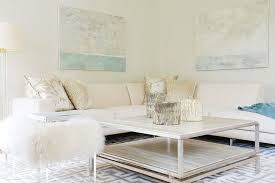 Chic Living Room Features Abstract Art Over Cream Sectional Sofa Accented With Gold Pillows And Sea Blue Throw Blanket Paired Square Coffee Table