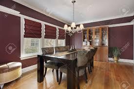 wohn esszimmer mit maroon wänden und drei fenstern
