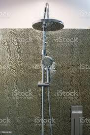 luxuriöse moderne edelstahl regendusche duscharmatur kopf und halter im badezimmer auf die goldene dekoration der decke fliesen wand hintergrund