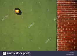 light fixture on green wall with brick wall border stock photo