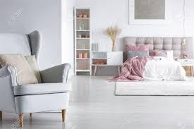 offenes schlafzimmer in einer weißen loft wohnung mit kissen auf bequemem stilvollem sessel und rosa metallic dekorationen