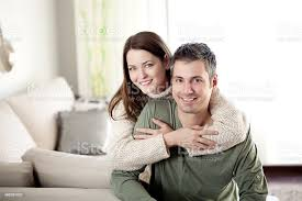junges paar lächelnd im wohnzimmer stockfoto und mehr bilder attraktive frau