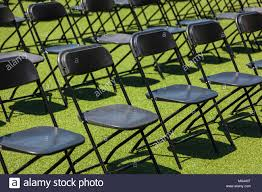 Rows Of Black Folding Chairs Setup For An Outdoor Event ...