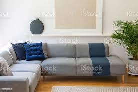 blaue kissen auf graue ecke im wohnzimmer interieur mit pflanze und poster echtes foto stockfoto und mehr bilder blau