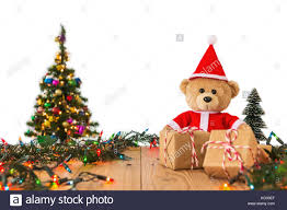 A Photo Of Teddy Bear In Santa Cross Dress With Christmas Tree Background