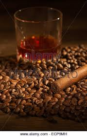 Selective Focus On The Cuban Cigar Lying Heap Of Coffee Beans Glass